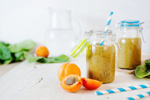 Healthy Food, Summer Drinks, Fruit And Vegetable Smoothie With Banana, Apricot And Spinach In Glass Bottles On A Light Background, Detox