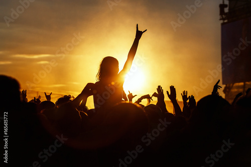 Young girl enjoys a rock concert, Silhouette on sunset, hands up on openair