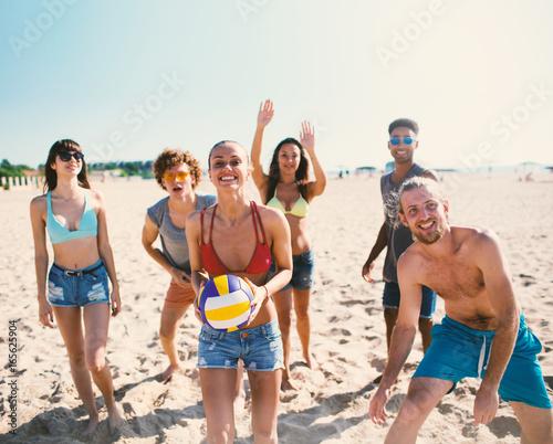 Plakat Grupa przyjaciele bawić się przy plażową salwą przy plażą