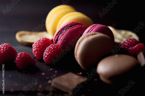 Aluminium Prints Macarons Group of colorful macarons with their ingredients over a wooden table