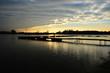 Molo na jeziorze na tle zachodzącego slońca i chmur