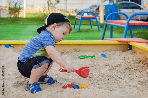 Charming cute boy playing in the sandbox on the playground Canvas Print