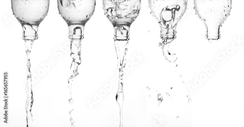 Leinwand Poster Pouring water from bottle glass isolated white background.