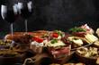 Italian antipasti wine snacks set. Cheese variety, Mediterranean olives, pickles, Prosciutto di Parma, tomatoes, artichokes and wine in glasses
