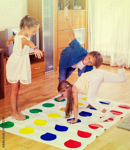 Fotografie, Obraz  Children playing twister at home.