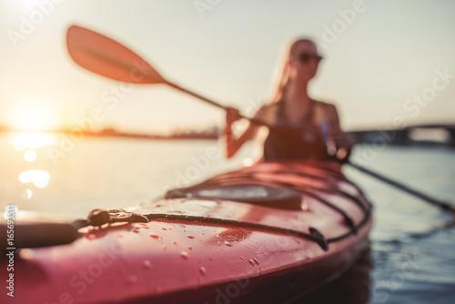 Fotografía  Woman kayaking on sunset