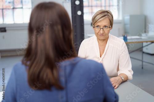ältere geschäftsfrau schaut eine kollegin ernst an Fotobehang