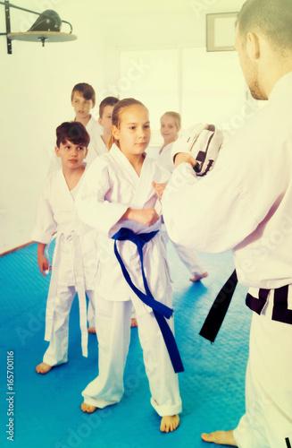 Children training karate kicks on punching bag during karate