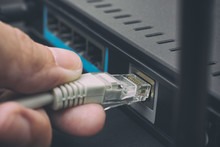 Person Plugging In Cable To Wireless Router