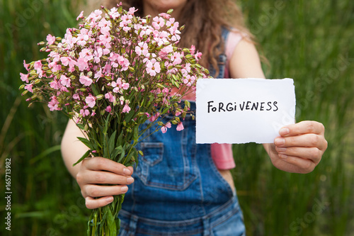 Fotografía  Forgiveness - woman with word and bouquet of pink flowers