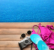 Beach set with camera for summer vacation on wooden pier near water