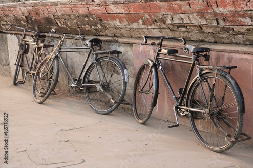 Foto auf AluDibond Fahrrad Old indian bicycles leaning on the temple wall.