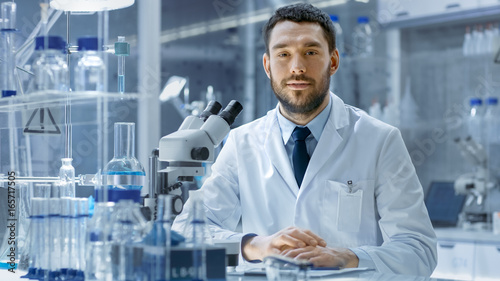 Young Male Research Looks into Camera and Smiles. He's Sitting in a High-End Modern Laboratory with Beakers, Glassware, Microscope and Working Monitors Surround Him.