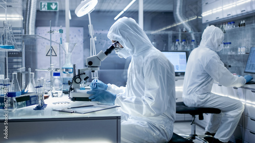 In a Secure High Level Laboratory Scientists in a Coverall Conducting a Research. Chemist Adjusts Samples in a  Petri Dish with Pincers.