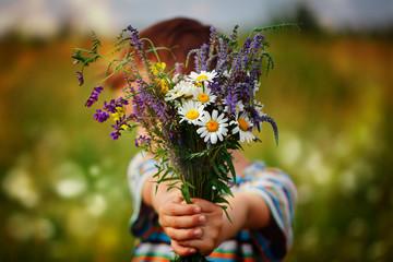 Little kid boy holding bouquet of fields flowers. Child giving flowers