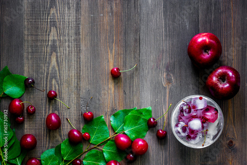 Apple, pulm, cherry, ice for summer fruit drink on wooden table background top view copyspace