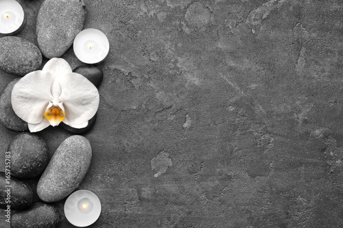 Composition with beautiful white orchid and stones on grey background
