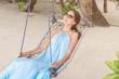 Beautiful young woman on swing at sea resort