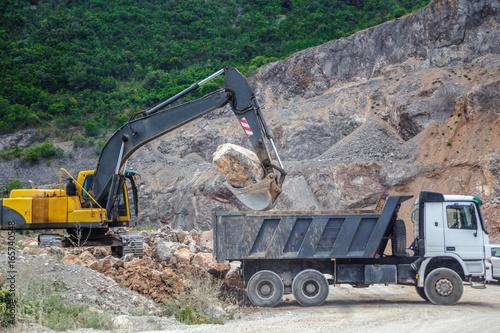 Plakat Koparka stawia ogromny kamień w ciężarówce