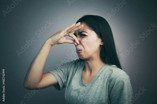 Valokuva  portrait headshot woman pinches nose with fingers