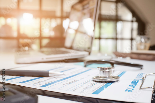 Carta da parati  Stethoscope on insurance policy with medical insurance, selective focus