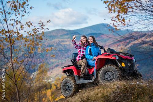 Smiling women in jackets on red ATV at the hill makes selfie on the phone with mountains in blurred background