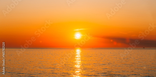 Poster Mer coucher du soleil Sun Is Setting On Horizon At Sunset Sunrise Over Sea Or Ocean.