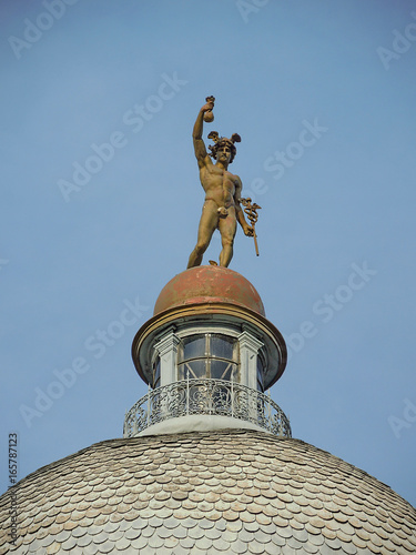 Photo Statue of Merkur/Hermes at the top of the dome of old building