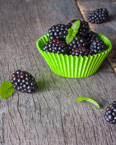 Fényképezés  Large blackberries in the form for a cupcake made of paper.