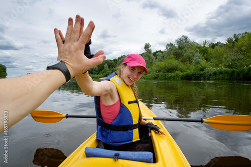 young girl in pink cap rowing in kayak over the river, giving high five to her t Tablou Canvas
