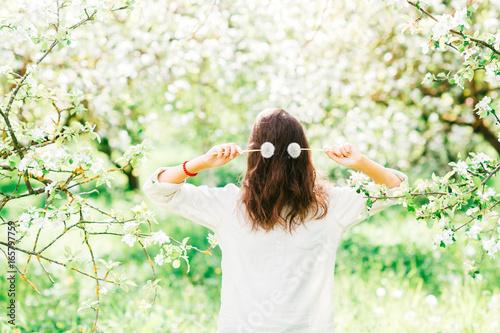 Fotografie, Obraz  Unrecognizable unknown brunette scarecro with hidden face standing in emerald blooming garden
