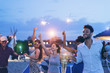 canvas print picture - Happy friends making evening beach party outdoor with fireworks and drinking champagne - Young people having fun at chiringuito bar with dj set - Focus on right man face - Youth and summer concept