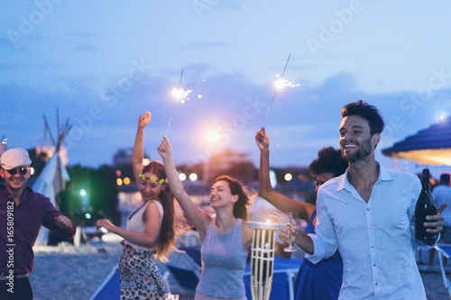 canvas print motiv - DisobeyArt : Happy friends making evening beach party outdoor with fireworks and drinking champagne - Young people having fun at chiringuito bar with dj set - Focus on right man face - Youth and summer concept