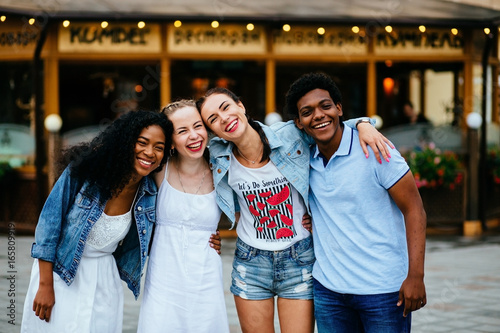 Fotografie, Tablou  Multiethnic group of four friends hugging and enjoying the summer outdoor in th city street