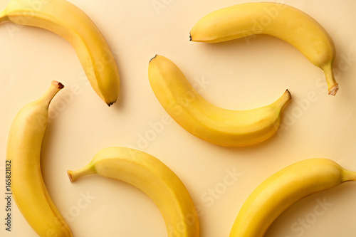 Banana pattern on a yellow background. Exotic fruit repetition viewed from above. Top view.