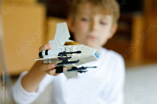 Happy little kid boy playing with space shuttle toy.