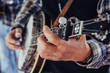 Musician's hands playing a banjo at a festival outdoors