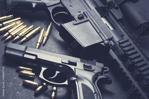 Handgun with rifle and ammunition on dark background Tapéta, Fotótapéta