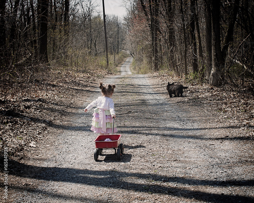 cute little girl pulling wagon with dog on wooded lane Canvas Print
