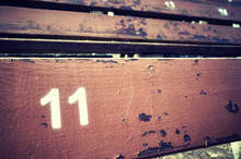 Number Eleven Painted On An Old Wooden Seat, Conceptual Picture With Copy Space On The Right.