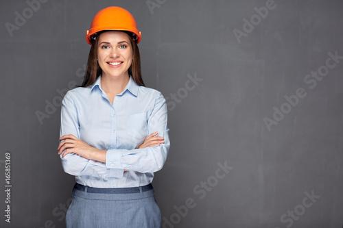 Smiling woman builder wearing safety helmet.