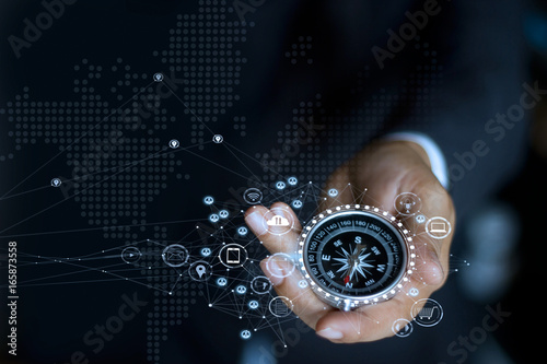 Businessman with a compass holding in hand Fototapeta