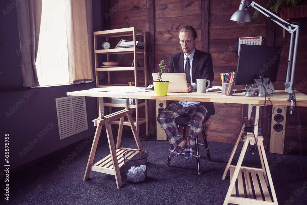 Fototapety, obrazy: Freelancer at working place at home. Man in jacket working with laptop, his legs in pajamas under table. Toned image.