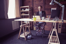 Freelancer At Working Place At Home. Man In Jacket Working With Laptop, His Legs In Pajamas Under Table. Toned Image.