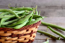 Fresh Green String Beans In A Wicker Basket. Young Green Beans, Good Source Of Fiber, Vitamins And Minerals. Wooden Background