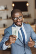 smiling handsome african american businessman holding money and showing thumb up