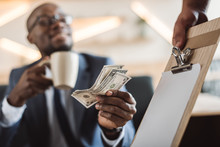 Selective Focus Of African American Businessman Paying With Cash In Cafe