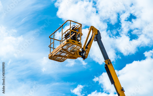 Fototapeta Hydraulic lift platform with bucket of yellow construction vehicle, heavy industry, blue sky and white clouds on background obraz