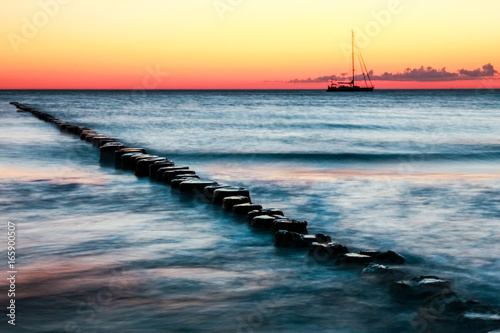 Wooden groynes and sailing boat. Red sunset and long exposure. Poster
