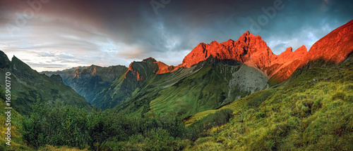 Amazing sunset and red afterglow in high mountains. Canvas Print